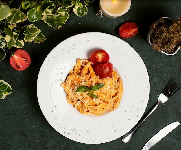 Pasta in salsa di pomodoro con parmigiano tritato, pomodoro e basilico.