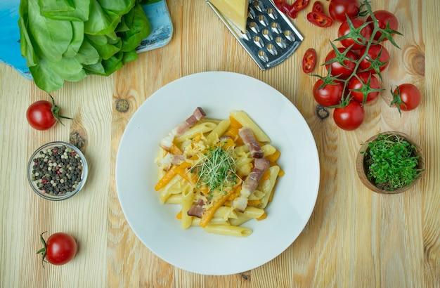 Pasta italiana con formaggio, zucca e pancetta fritta