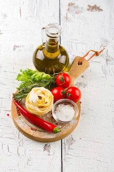Pasta italiana con pomodori, olio d'oliva e rosmarino su una tavola di legno bianca