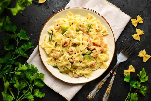 Pasta italiana con salsa cremosa con gambero su una zolla, vista superiore. farfalle con gamberi su un tavolo scuro.
