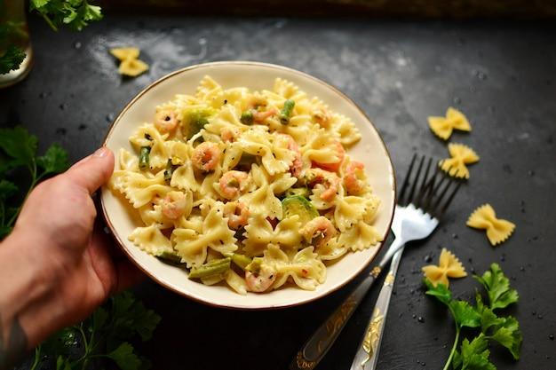 Pasta italiana con salsa cremosa con gambero su una zolla, vista superiore. farfalle di gamberetti su un tavolo scuro. mani nel telaio. la ragazza tiene un bellissimo piatto con pasta alimentare.