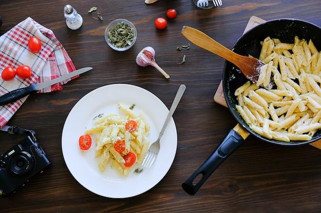 Pasta italiana con salsa, formaggio, pomodori e spezie su un piatto bianco e in padella su un tavolo di legno.