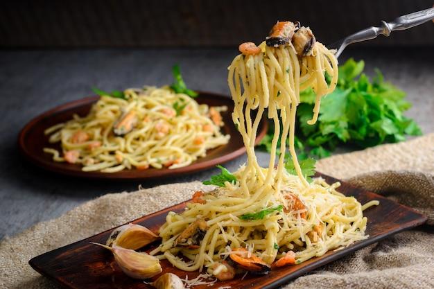 Pasta italiana in salsa cremosa con frutti di mare, gamberetti e cozze su un piatto