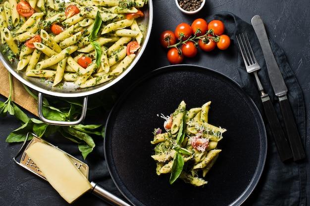 Pasta italiana penne con spinaci, pomodorini e basilico.