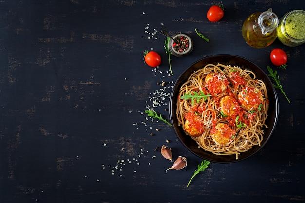Pasta italiana spaghetti con polpette di carne e parmigiano in lamiera nera