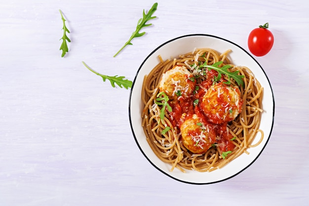 Pasta italiana. spaghetti con polpette e parmigiano in ciotola su fondo di legno rustico leggero. cena. vista dall'alto. concetto di cibo lento