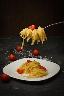 Pasta italiana su un piatto su un buio con pomodorini