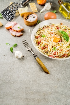 Pasta italiana tradizionale, spaghetti alla carbonara con pancetta, salsa cremosa, parmigiano, tuorlo d'uovo e basilico fresco