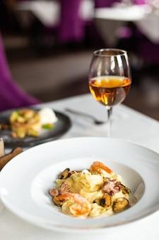 Pasta kraft di frutti di mare: cozze, gamberi e polpo in salsa cremosa, serviti su un piatto bianco su un tavolo con una tovaglia bianca, strumenti e un bicchiere di vino in un ristorante