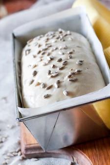 Pasta lievitata cruda a forma di latta, pronta per cuocere il pane con semi di girasole
