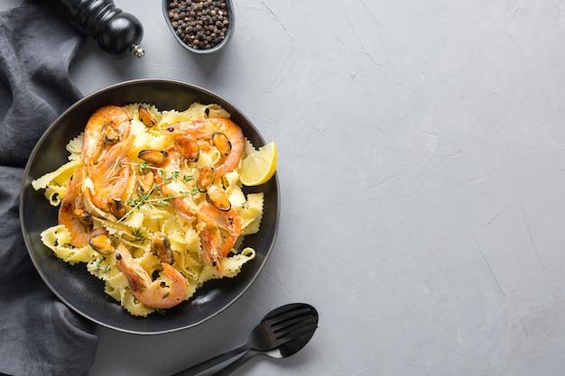 Pasta mafaldine o reginelle con frutti di mare, gamberi, cozze sul tavolo grigio. copia spazio. vista dall'alto