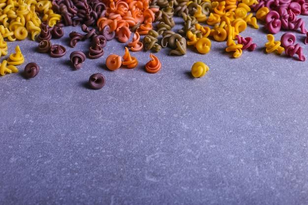 Pasta multicolore di forma insolita con coloranti vegetali naturali, sparsi sul tavolo primo piano di sfondo.