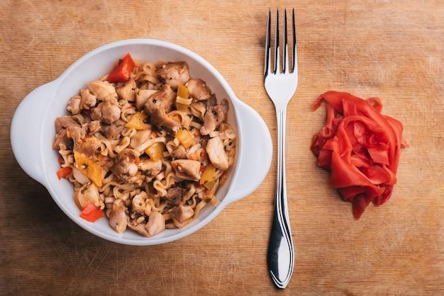 Pasta o tagliatelle asiatiche con verdure e carne con salsa piccante su tavola di legno con forchetta