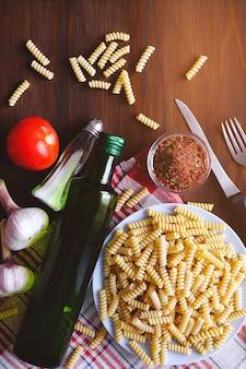Pasta, olio d'oliva, pomodori, aglio, su un tavolo di legno.