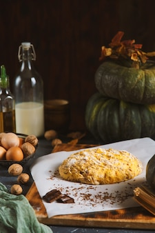 Pasta per biscotti e ingredienti per la preparazione di biscotti su uno sfondo di legno scuro