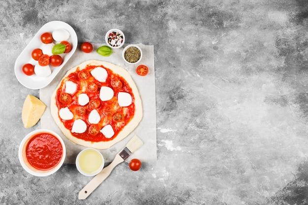 Pasta per pizza e ingredienti per pizza su spazio grigio. vista dall'alto, copia spazio. spazio alimentare