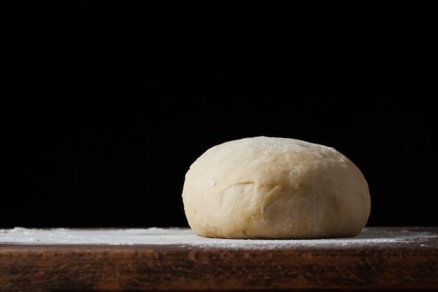 Pasta per pizza o cottura su uno sfondo scuro.