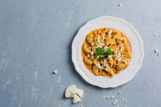 Pasta pipa il rigat con salsa di ceci e pomodori, cosparsa di formaggio feta e coriandolo