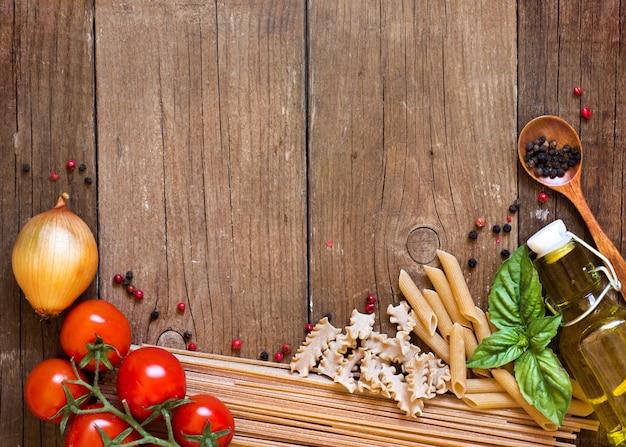 Pasta, pomodori, cipolla, olio d'oliva e basilico sulla vista superiore del fondo di legno