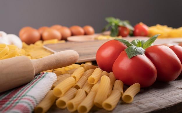 Pasta, pomodori e ingredienti per ristorante italiano con impastatrice in legno