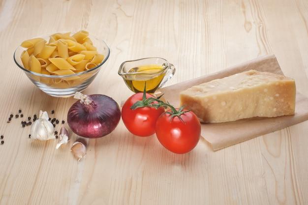Pasta, pomodori, formaggio, aglio sul tavolo