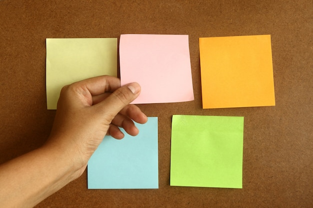 Pasta post-it colorata su superficie marrone