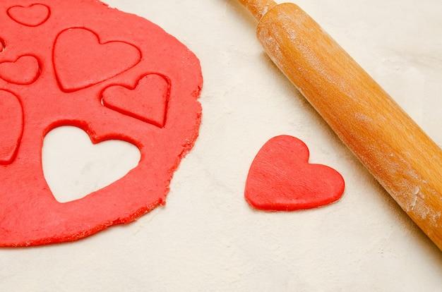 Pasta rossa con un mattarello e cuori tagliati su una tavola bianca, primo piano