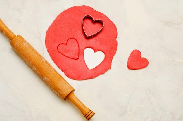 Pasta rossa con un mattarello e ritagliare i cuori su un tavolo bianco