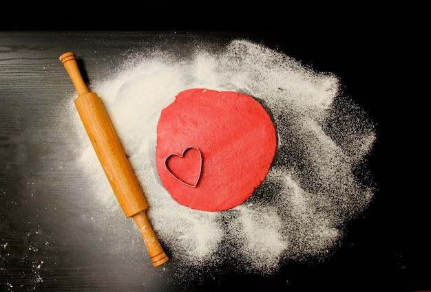 Pasta rossa per formare cuori ritagliati e farina sul tavolo nero, un mattarello. vista dall'alto