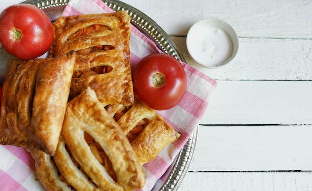 Pasta sfoglia con pomodoro su un tavolo in legno bianco con spazio di copia