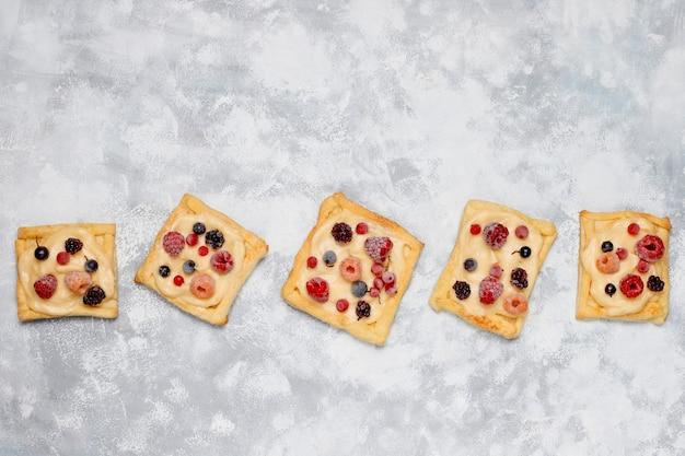 Pasta sfoglia deliziosa fresca con le bacche dolci su calcestruzzo