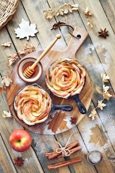 Pasta sfoglia fatta in casa con fette di mela a forma di rosa cotte in padelle di ferro su legno