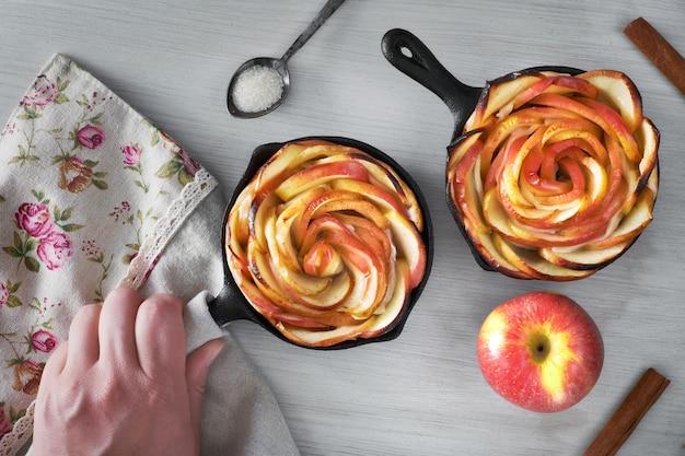 Pasta sfoglia fatta in casa con fettine di mela a forma di rosa cotte in padelle di ferro