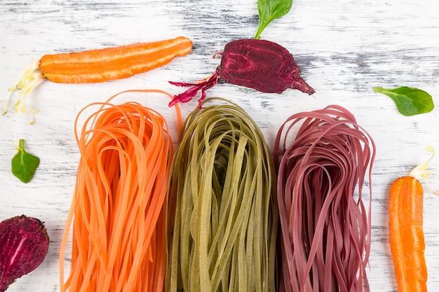 Pasta vegetariana colorata di verdure crude con barbabietole, carote e spinaci.