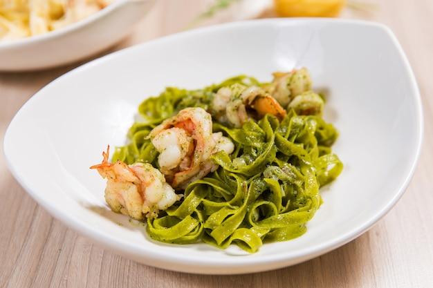 Pasta verde con gamberi e formaggio in zolla bianca sul tavolo in legno chiaro in un ristorante