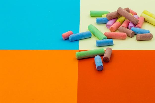 Pastelli colorati su uno sfondo di carta diversa