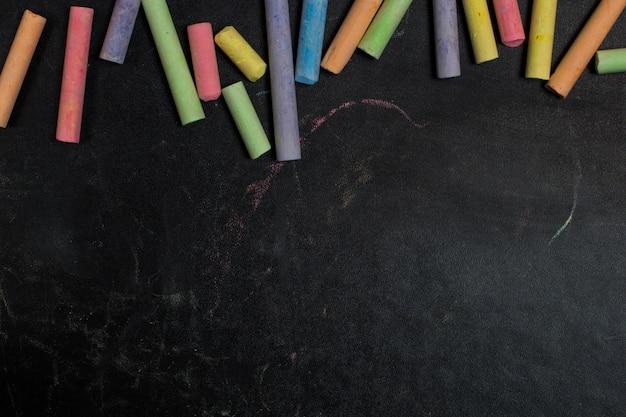 Pastelli colorati su uno sfondo di lavagna.
