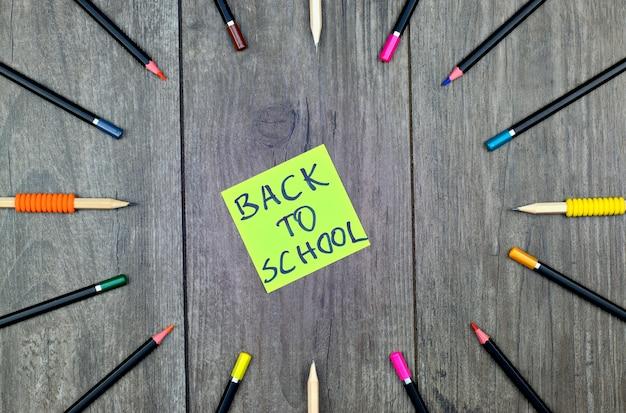 Pastelli delle matite e rifornimenti di scuola su un fondo di legno con una carta di ritorno a scuola