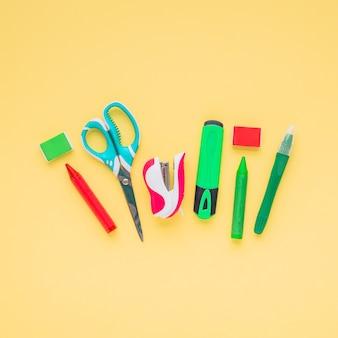 Pastelli; forbice; evidenziatore; spillatrice e gomma disposti in superficie gialla