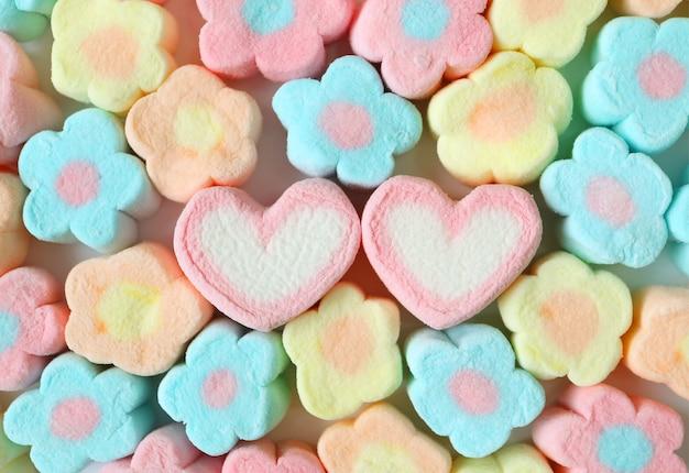 Pastello blu e giallo a forma di fiore con una coppia di marshmallow a forma di cuore
