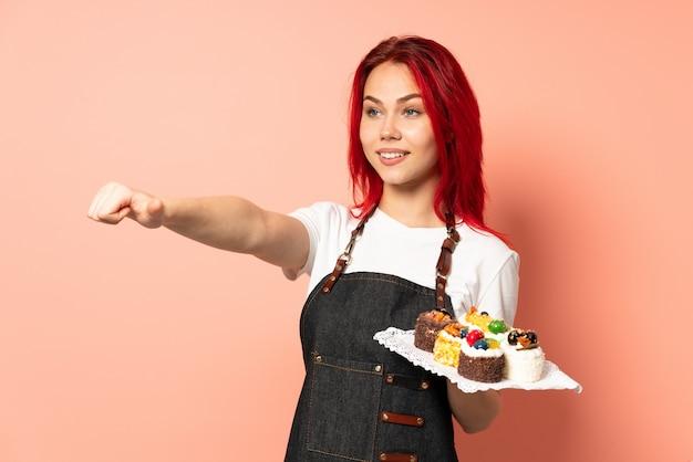 Pasticcere che giudica muffin isolato sulla parete rosa che dà un pollice in alto gesto