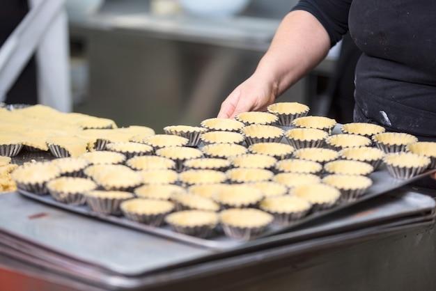 Pasticcere che prepara le tortine, mettendo l'impasto in piatti da forno, nella cucina della pasticceria.