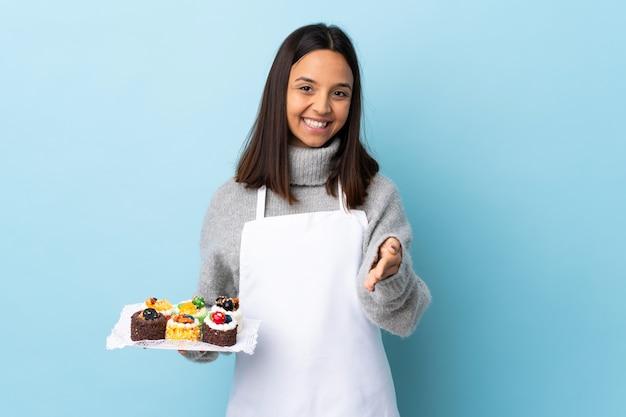Pasticcere che tiene una grande torta sopra fondo blu isolato che stringe le mani per chiudere molto