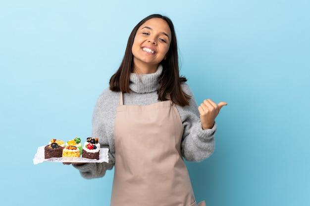 Pasticcere che tiene una grande torta sopra la parete blu con i pollici aumenta il gesto e sorridere