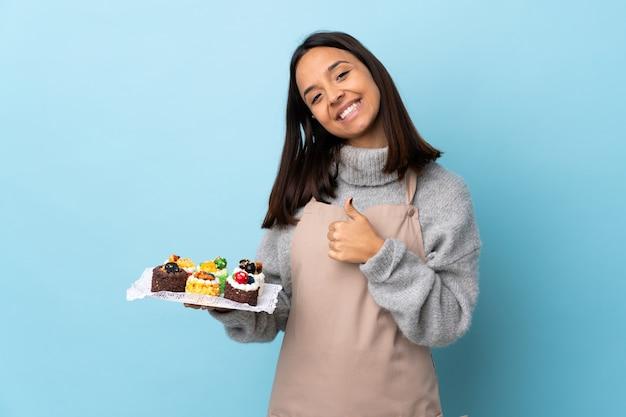 Pasticcere che tiene una grande torta sopra la parete blu isolata che dà un pollice in su gesto