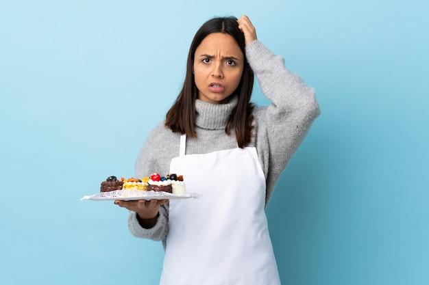 Pasticcere che tiene una grande torta sopra la parete blu isolata con un'espressione di frustrazione e di non comprensione