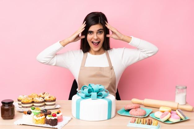Pasticcere con una grande torta in un tavolo sopra il muro rosa con espressione sorpresa