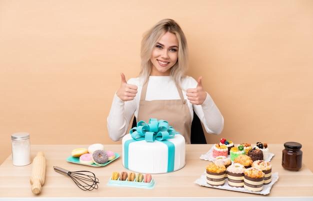 Pasticcere dell'adolescente con una grande torta in una tavola che dà un pollice in su gesto