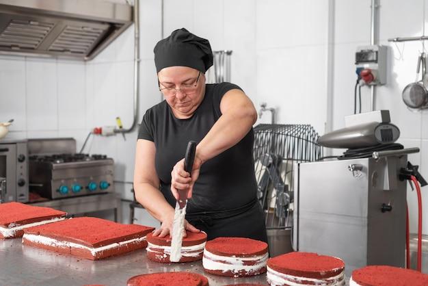 Pasticcere della donna che sorride e che lavora felice, facendo le torte alla pasticceria.
