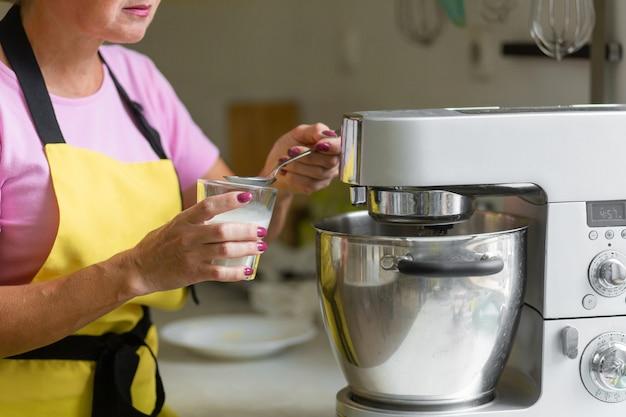 Pasticcere professionista della donna che prepara un dessert. aggiunge ingredienti e mescola l'impasto in un mixer